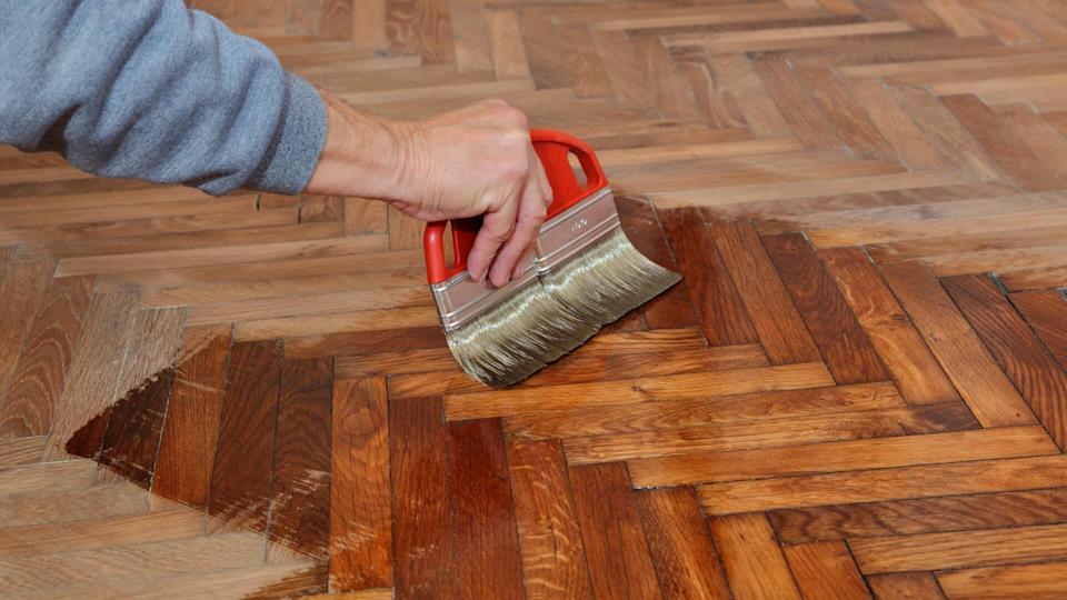 Varnishing of oak parquet floor, workers hand and brush.